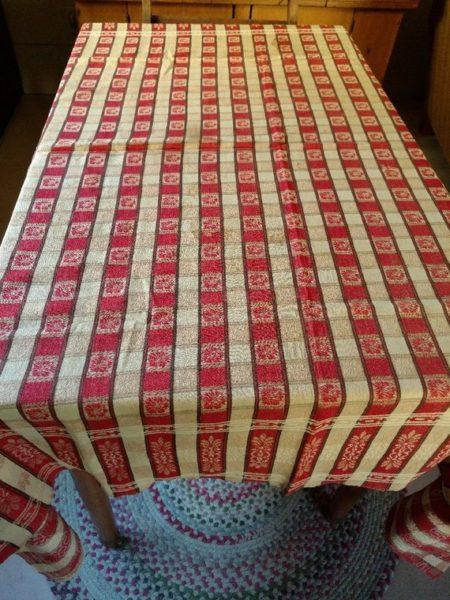 For the love of turkey red, The Gatherings is offering a Victorian, early 1900's tablecloth in a woven stylized design. The cloth features a red and tan stripe check.  Each check alternates with a flower, or leaf design through the center and along the two long sides.   A border on the two short sides, features the stylized pattern.   A typical style cloth one would find on a farm house kitchen table.  Cozy charm!